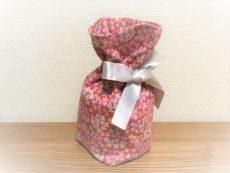 ピンク生地に花柄の骨入れ袋。