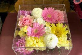 アクリルケースに収められている、ピンクのガーベラやバラなどの花々。
