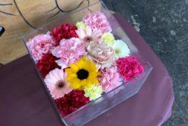 アクリルケースの納められている、ひまわりやガーベラなどの花々。